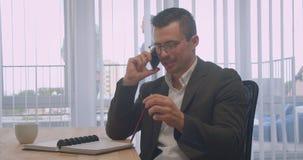 Портрет крупного плана привлекательного бизнесмена в стеклах имея телефонный звонок и принимая примечания в офис внутри помещения сток-видео