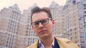 Портрет крупного плана привлекательного кавказского бизнесмена смотря вперед и после этого указывая вне палец на камере с видеоматериал