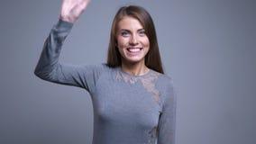Портрет крупного плана привлекательной молодой кавказской женщины получая удивленный смотрящ камеру усмехаясь и развевая с ей видеоматериал