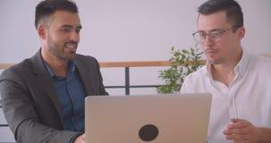Портрет крупного плана 2 привлекательных бизнесменов обсуждая проект на ноутбуке совместно в офисе внутри помещения сток-видео