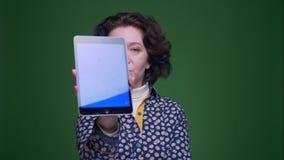 Портрет крупного плана старого кавказского брюнета женского используя планшет и показывать голубой экран chroma к камере с видеоматериал