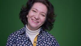 Портрет крупного плана старой кавказской женщины брюнета поворачивая и смотря камеру усмехаясь жизнерадостно с предпосылкой видеоматериал