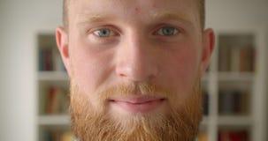 Портрет крупного плана студентов redhead бородатых кавказских смотрит на усмехаться счастливо смотрящ камеру в библиотеке акции видеоматериалы
