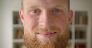 Портрет крупного плана студентов redhead бородатых кавказских смотрит на усмехаться жизнерадостно смотрящ камеру в библиотеке видеоматериал