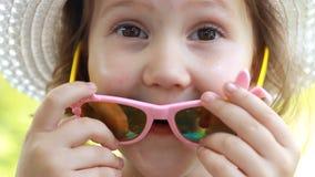 Портрет крупного плана счастливого ребенка в шляпе и солнечных очках усмехаясь и смеясь, выражая эмоции счастья Отрежьте сток-видео