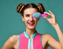 Портрет крупного плана счастливого рта конца женщины брюнет моды с красочной розовой голубой желтой малой щеткой гребня волос Стоковые Изображения RF