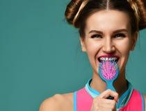 Портрет крупного плана счастливого рта конца женщины брюнет моды с красочной розовой голубой желтой малой щеткой гребня волос Стоковые Изображения