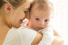 Портрет крупного плана счастливой усмехаясь матери и прелестных 3 месяцев старого младенца в солнце излучает Стоковые Изображения