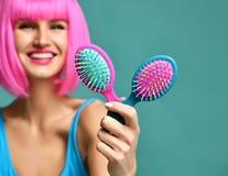 Портрет крупного плана счастливые щетки гребня волос владением 2 женщины брюнет моды малой розовой голубой желтой малой в розовом Стоковые Изображения RF