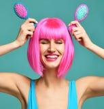 Портрет крупного плана счастливые щетки гребня волос владением 2 женщины брюнет моды малой розовой голубой малой в розовом парике Стоковые Фотографии RF
