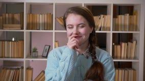 Портрет крупного плана усмехаться молодой милой студентки nossing смотрящ камеру в университетской библиотеке внутри помещения видеоматериал