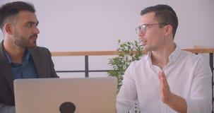 Портрет крупного плана 2 успешных бизнесменов обсуждая проект на ноутбуке совместно в офисе внутри помещения видеоматериал