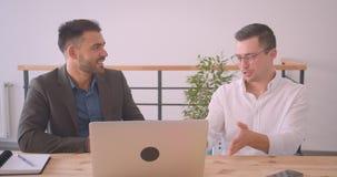 Портрет крупного плана 2 успешных кавказских бизнесменов обсуждая проект на ноутбуке совместно в офисе видеоматериал