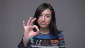 Портрет крупного плана handsign ок показа взрослого кавказского брюнета женского смотря камеру с предпосылкой изолированной дальш сток-видео