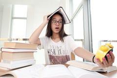 Портрет крупного плана белой женщины окруженный тоннами книг, будильника, усиленного от крайнего срока проекта, исследование, экз стоковое изображение rf