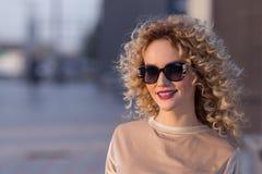 Портрет крупного плана белокурой девушки при короткие волосы представляя на steet на предпосылке захода солнца Стоковые Изображения RF