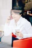 Портрет крупного плана бизнес-леди среднего возраста кавказской белой сидя в ресторане кафа при чашка кофе говоря сверх на телефо Стоковые Фото
