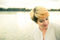 Портрет крупного плана красивой девушки с короткими светлыми волосами на заходе солнца на озере Стоковые Фотографии RF