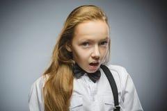 Портрет крупного плана красивой девушки с удивленным выражением пока стоящ против серой предпосылки Стоковое Изображение