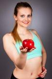 Портрет крупного плана красивой молодой женщины показывая красное яблоко Стоковая Фотография