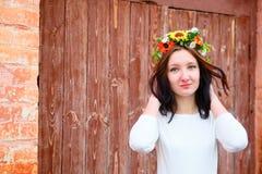 Портрет крупного плана красивой молодой женщины с венком цветка на ее голове около деревянной двери Стоковое Изображение