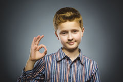 Портрет крупного плана красивый усмехаться подростка и о'кей выставки над серой предпосылкой Стоковое Фото
