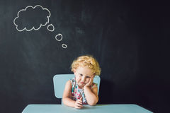 Портрет крупного плана милой маленькой девочки думая глубоко о somet Стоковое фото RF