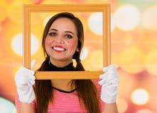 Портрет крупного плана милой пантомимы клоуна маленькой девочки держа деревянную рамку перед ее стороной Стоковые Фотографии RF