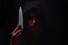 Портрет крупного плана молодого человека в hoodie, держа нож внутри стоковое фото rf