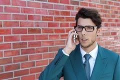 Портрет крупного плана, молодой человек надоел, расстроил, помоченный кто-то слушая на его мобильном телефоне, плохая новость, ou стоковое фото