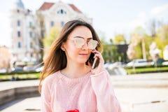 Портрет крупного плана наслаженной девушки брюнет в солнечных очках говоря на телефоне на улице Стоковое Изображение