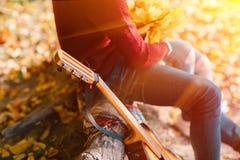 Портрет крупного плана пары сидя с гитарой около костра в лесе Стоковые Фото