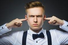 Портрет крупного плана потревоженного мальчика покрывая его уши, наблюдающ не те ничего Человеческие эмоции, выражения лица стоковое изображение rf