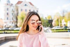 Портрет крупного плана положительной девушки брюнет говоря на телефоне на солнечной улице Стоковое Изображение RF