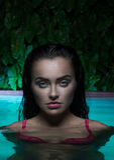 Портрет крупного плана сексуальной женщины брюнет нося розовое бикини стоя в бассейне Стоковые Изображения