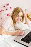 портрет крупного плана счастливой усмехаясь красивой нежной сладостной молодой девушки голубых глазов бизнес-леди в кровати работ Стоковое Изображение