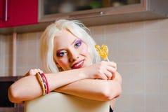 Портрет крупного плана усмехаясь белокурой девушки с конфетой Стоковое Изображение