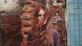 Портрет крупного плана redheaded девушки с загадочным взглядом девушка с веснушками смотрит камеру Летание волос в ветре сток-видео