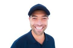 Портрет крышки жизнерадостного работника доставляющего покупки на дом нося Стоковые Фото