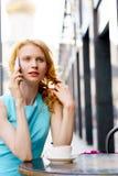 Портрет курчавой белокурой женщины говоря на мобильном телефоне в кафе Стоковое Фото