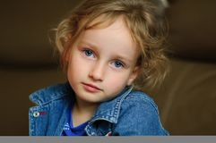 Портрет курчавой голубоглазой девушки с спокойным взглядом Она носит жилет джинсовой ткани Стоковое фото RF