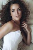 Портрет курчавой темн-с волосами молодой красивой девушки в белом co Стоковые Изображения RF