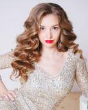 Портрет курчавых молодых женщин в платье золота яркого блеска с губами совершенного состава красными на белой предпосылке Концепц Стоковая Фотография RF