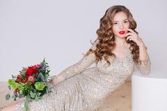 Портрет курчавых молодых женщин в платье золота яркого блеска с губами совершенного состава красными на белой предпосылке Концепц стоковые изображения rf