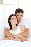 портрет любовников кровати счастливый обнимая их Стоковая Фотография RF