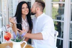 Портрет любовников, человек фотографирует по телефону по мере того как он целует его любимое девушка сидит с парнем в кафе, стоковое фото rf
