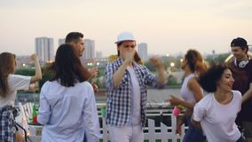 Портрет людей и друзей женщин стоя с унылыми сторонами на крыше party после этого внезапно начинающ танцевать и смеяться над видеоматериал