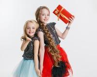 Портрет маленьких девочек при курчавый стиль причёсок стоя на партии праздника в платье с sequins, держа настоящий момент Стоковые Фотографии RF