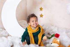 Портрет маленького афроамериканца Улыбки младенца Черный мальчик в зеленом свитере и желтом усмехаться шарфа Немногое принц C стоковое фото