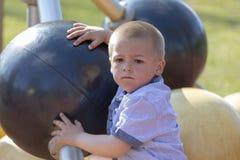 Портрет маленького белокурого мальчика на спортивной площадке стоковое изображение